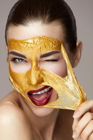 Beauty Product. Portret Van Sexy Gezond Meisje Verwijderen, Peeling Cosmetische Gouden Masker Van Mooie Gezicht Huid. Close-up Van Aantrekkelijke Jonge Vrouw Met Verse Huid En Heldere Make-up. Hoge resolutie