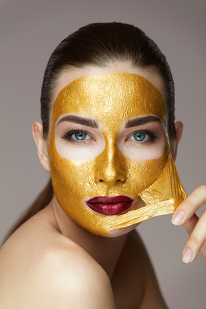Woman Face Beauty. Closeup Beautiful Sexy Girl Taking Off Cosmetic Peeling Gold Mask From Healthy Skin. Portrait Of Attractive Young Female With Bright Makeup Removing Beauty Product. High Resolution Standard-Bild