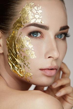 女性のスキンケア。美金で若い女性モデルのポートレート マスク新鮮な肌に触れます。自然なメイクと顔を Caressing 手でセクシーな女性のクローズ