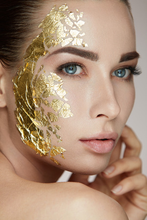 Woman Skin Care. Portrait Of Young Female Model With Beauty Gold Mask Touching Facial Fresh Skin. Closeup Of Sexy Woman With Natural Makeup And Hand Caressing Face. Cosmetic Concept. High Resolution Stock Photo