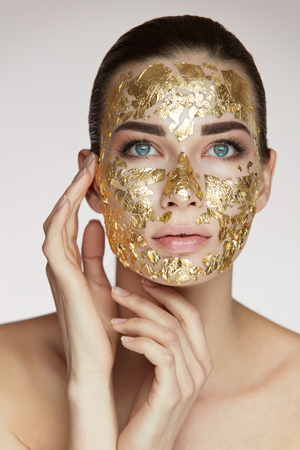 Woman Face Beauty. Portrait Of Beautiful Female Holding Hands Near Head And Golden Mask On Face Skin. Closeup Sexy Girl With Natural Makeup And Skin Cosmetics Product On Facial Skin. High Resolution