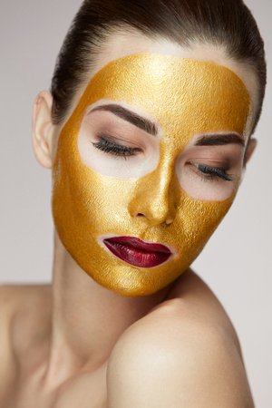 Woman Face Treatment. Portrait Of Beautiful Young Female With Cosmetic Gold Mask On Beauty Face. Closeup Of Attractive Sexy Girl With Bright Professional Makeup And Soft Smooth Skin. High Resolution Stock fotó - 81118466