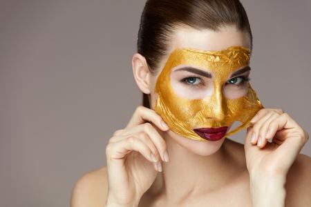 뷰티 화장품. 매력적인 젊은여자가 손 을와 부드러운 얼굴에서 골드 마스크를 제거의 초상화. 부드러운 피부와 섹시 한 글 래 머 메이크업 아름 다운