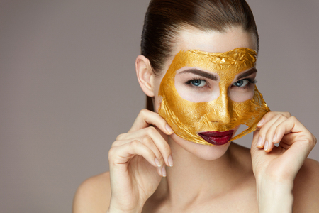 Beauty Cosmetics. Portrait Of Attractive Young Woman Removing Gold Mask From Smooth Face With Hands. Closeup Of Beautiful Healthy Female Model With Soft Skin And Sexy Glamour Makeup. High Resolution Stok Fotoğraf