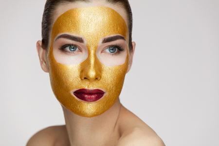 美容化粧品。ゴールド化粧品顔にマスクの柔らかい肌と健康な若い女性のクローズ アップ。新鮮な肌に顔製品で美しいセクシーな女性モデルのポー 写真素材