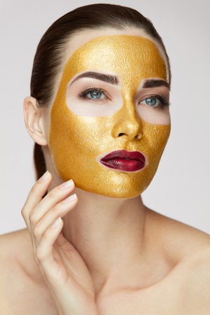 Cosmetic Product. Portrait Of Beautiful Healthy Girl With Beauty Gold Mask. Closeup Of Attractive Young Woman With Smooth Skin And Fresh Makeup Touching Face. Facial Care Procedure. High Resolution