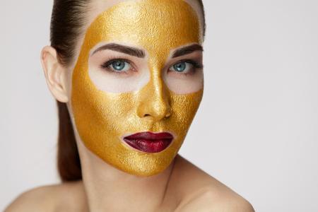 Cosmética de belleza. Primer plano de mujer joven sana con mascarilla cosmética oro sobre piel suave. Retrato de hermosa mujer sexy modelo con producto facial en piel fresca. Cuidado facial. Alta resolución Foto de archivo