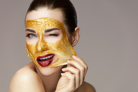 Woman Face Beauty. Closeup Beautiful Sexy Girl Taking Off Cosmetic Peeling Gold Mask From Healthy Skin. Portrait Of Attractive Young Female With Bright Makeup Removing Beauty Product. High Resolution Stock Photo