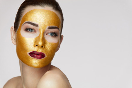 Woman Face Treatment. Portrait Of Beautiful Young Female With Cosmetic Gold Mask On Beauty Face. Closeup Of Attractive Sexy Girl With Bright Professional Makeup And Soft Smooth Skin. High Resolution