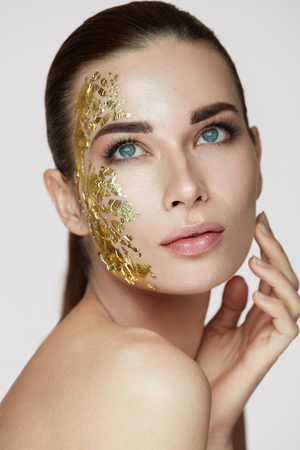 Vrouw huidverzorging. Portret van jonge vrouwelijke Model met schoonheid gouden masker aanraken Facial frisse huid. Close-up van sexy vrouw met natuurlijke make-up en met de hand strelen gezicht. Cosmetisch Concept. Hoge resolutie
