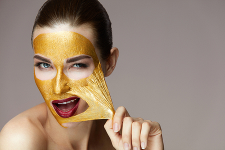 Woman Face Beauty. Closeup Beautiful Sexy Girl Taking Off Cosmetic Peeling Gold Mask From Healthy Skin. Portrait Of Attractive Young Female With Bright Makeup Removing Beauty Product. High Resolution Archivio Fotografico