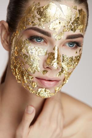 스파 절차. 몸을 애 태우는 얼굴 피부에 골드 마스크와 섹시 한 여자의 초상화. 부드러운 피부와 화장품 제품 얼굴에 매력적인 여자의 근접 촬영. 아름