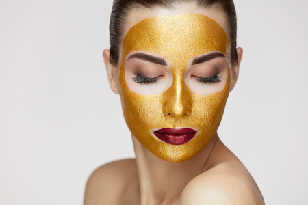 Beauty Cosmetics. Closeup Of Healthy Young Woman With Gold Cosmetic Face Mask On Soft Skin. Portrait Of Beautiful Sexy Female Model With Face Product On Fresh Skin. Facial Care. High Resolution Reklamní fotografie - 81118485