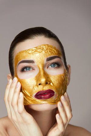 Facial Skin Cosmetics. Closeup Of Beautiful Young Female Model With Gold Mask Caressing Face With Hands. Portrait Of Attractive Healthy Girl With Soft Skin And Fresh Makeup. High Resolution