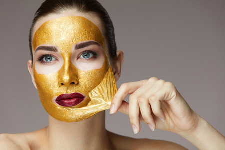 뷰티 제품. 섹시 한 건강 한 여자 제거, 아름 다운 얼굴 피부에서 화장품 골드 마스크를 필 링의 초상화. 신선한 피부와 밝은 메이크업 매력적인 젊은  스톡 콘텐츠