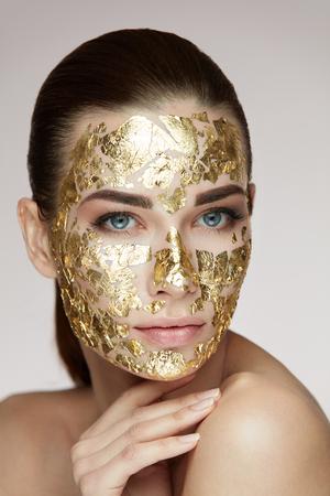 Spa-procedure. Portret Van Sexy Meisje Met Gouden Masker Op Gezicht Huid Caressing Body. Close-up Van Aantrekkelijke Vrouw Met Gladde Huid En Kosmetisch Product Op Gezicht. Schoonheidskoncept. Hoge resolutie Stockfoto