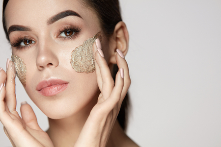 Woman Face Skin Care. Closeup Beautiful Young Female Model With Natural Makeup Applying Scrub On Face. Portrait Of Attractive Girl Touching Soft Facial Skin With Cosmetic Product On. High Resolution Standard-Bild