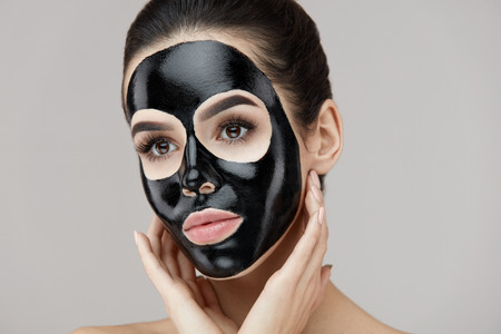 Woman Face With Black Peeling Mask On Skin. Portrait Of Beautiful Young Female Applying Cosmetic Mask On Face. Closeup Of Attractive Girl Model With Skin Care Product On Facial Skin. High Resolution Stock Photo