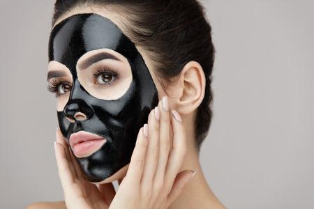 여자 뷰티 스킨 케어 스킨 케어. 얼굴 피부에 검은 부드러운 껍질 마스크를 적용하는 매력적인 여자의 근접 촬영. 자연스러운 메이크업 및 화장품 껍질