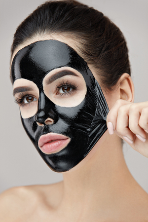 여자 얼굴 관리입니다. 얼굴 피부에서 화장품 블랙 필 링 마스크를 제거하는 아름 다운 여자의 초상화. 자연스러운 메이크업 및 화장품 껍질 마스크 얼