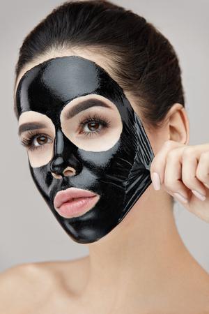 Vrouw Gezichtsverzorging. Portret Van Mooi Meisje Verwijder Kosmetische Zwarte Peeling Masker Van Gezichtshuid. Close-up Van Aantrekkelijke Jonge Vrouw Met Natuurlijke Make-up En Kosmetische Peelmasker Op Gezicht. Hoge resolutie Stockfoto
