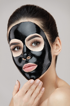 Beauty Skin Care Product. Portrait Of Sexy Young Woman With Black Peel Mask On Face. Closeup Of Healthy Beautiful Female With Natural Makeup Applying Black Peeling Mask On Facial Skin. High Resolution Stock Photo - 81438282