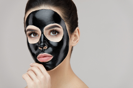 Beauty Face Care. Portrait Of Sexy Young Girl With Black Exfoliating Cosmetic Mask On Skin. Closeup Of Beautiful Female Model With Natural Makeup Applying Black Peeling Mask On Face. High Resolution