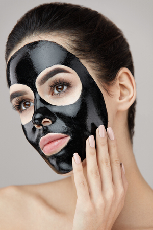 Beauty Skin Care Product. Portrait Of Sexy Young Woman With Black Peel Mask On Face. Closeup Of Healthy Beautiful Female With Natural Makeup Applying Black Peeling Mask On Facial Skin. High Resolution Stock Photo