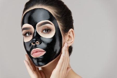 피부에 검은 필 링 마스크와 여자 얼굴. 얼굴에 화장품 마스크를 적용하는 아름 다운 젊은 여성의 초상화. 매력적인 여자 모델 얼굴 피부에 스킨 케어  스톡 콘텐츠
