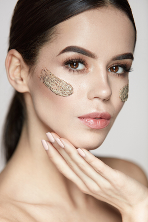 Woman Face Skin Care. Portrait Of Beautiful Healthy Girl Touching Face With Beauty Product, Cosmetic Peeling Mask On Fresh Soft Skin. Closeup Of Sexy Female With Scrub On Facial Skin. High Resolution Stock Photo