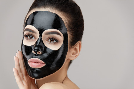 Female Beauty Face Skin Treatment. Closeup Beautiful Sexy Young Woman With Natural Makeup And Cosmetic Black Peel Mask On Facial Skin. Attractive Girl Applying Peeling Product On Face. High Resolution Stock Photo