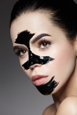 Beauty Cosmetics. Closeup Beautiful Young Female With Natural Makeup And Black Peel Off Mask On Skin. Closeup Of Attractive Woman With Cosmetic Skin Care Peeling Product On Face. High Resolution