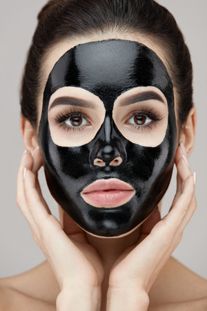 Woman Face With Black Peeling Mask On Skin. Portrait Of Beautiful Young Female Applying Cosmetic Mask On Face. Closeup Of Attractive Girl Model With Skin Care Product On Facial Skin. High Resolution Stock Photo - 81438180