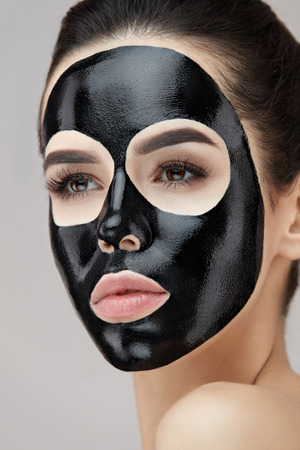 Beautiful Woman Face With Facial Beauty Mask On Skin. Closeup Female With Natural Makeup And Black Peeling Mask On Face. Portrait Of Gorgeous Girl Model With Peel Off Mask. Cosmetics. High Resolution Stock Photo