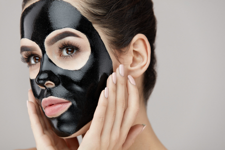 Woman Beauty Face Skin Care. Closeup Of Attractive Girl Applying Black Smooth Peeling Mask On Facial Skin. Portrait Of Beautiful Female With Natural Makeup And  Cosmetic Peel Off Mask. High Resolution