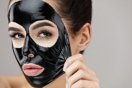 女性の顔のケア。美少女顔の皮膚からマスクを剥離化粧品黒の取り外しの肖像画。自然化粧品と化粧品皮マスク顔に魅力的な若い女性のクローズ ア