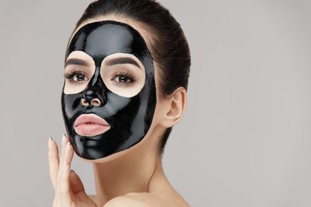 Tratamiento de la piel de cara de belleza femenina. Mujer joven atractiva hermosa del primer con maquillaje natural y máscara cosmética de la cáscara negra en piel facial. Muchacha atractiva que aplica el producto de la peladura en cara. Alta resolución Foto de archivo - 81438188
