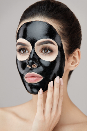 Beauty Skin Care Product. Portrait Of Sexy Young Woman With Black Peel Mask On Face. Closeup Of Healthy Beautiful Female With Natural Makeup Applying Black Peeling Mask On Facial Skin. High Resolution Stock Photo - 81438191