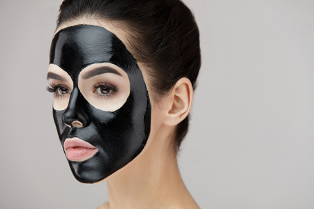 Beauty Face Cosmetics. Closeup Of Young Female With Natural Makeup And Black Peel Off Mask On Facial Skin. Portrait Of Attractive Woman With Cosmetic Peeling Product On Beautiful Face. High Resolution Stock Photo