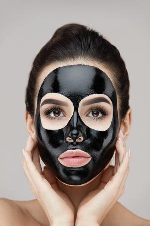 Fronte della donna con la mascherina nera della sbucciatura su pelle. Ritratto di bella giovane femmina applicando la maschera cosmetica sul viso. Primo piano del modello attraente della ragazza con il prodotto di cura di pelle su pelle facciale. Alta risoluzione Archivio Fotografico - 81438202
