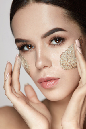 Woman Face Skin Care. Closeup Beautiful Young Female Model With Natural Makeup Applying Scrub On Face. Portrait Of Attractive Girl Touching Soft Facial Skin With Cosmetic Product On. High Resolution 版權商用圖片