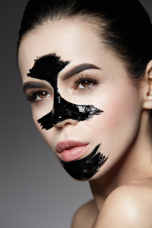 Beauty Cosmetics. Closeup Beautiful Young Female With Natural Makeup And Black Peel Off Mask On Skin. Closeup Of Attractive Woman With Cosmetic Skin Care Peeling Product On Face. High Resolution Stock Photo - 81438208