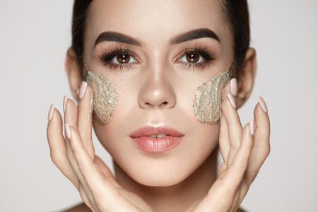 여자 스킨 케어 얼굴. 근접 촬영 얼굴에 스크럽을 적용하는 천연 메이크업으로 아름 다운 젊은 여성 모델. 화장품 제품을 가진 부드러운 얼굴 피부를