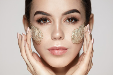 Woman Face Skin Care. Closeup Beautiful Young Female Model With Natural Makeup Applying Scrub On Face. Portrait Of Attractive Girl Touching Soft Facial Skin With Cosmetic Product On. High Resolution Archivio Fotografico