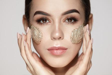 Vrouw Gezicht Huidverzorging. Close-up Mooi Jong Vrouwelijk Model Met Natuurlijke Make-up Toepassing Scrub Op Gezicht. Portret Van Aantrekkelijk Meisje Aan Aanraken Zachte Gezichtshuid Met Kosmetisch Product Aan. Hoge resolutie