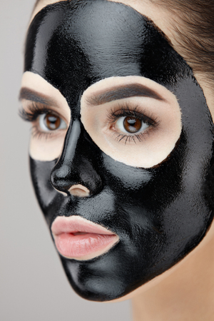 Cosmetology. Portrait Of Beautiful Female With Black Peeling Mask On Face. Closeup Of Healthy Young Woman With Fresh Natural Makeup And Cosmetic Beauty Product. Skin Care Treatment. High Resolution Stock Photo