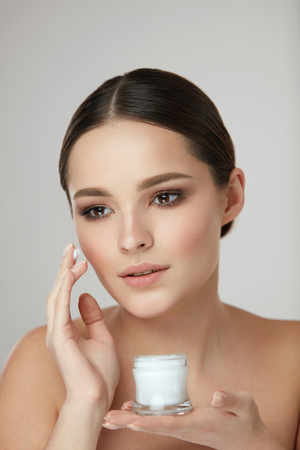 Woman Beauty Cosmetics. Closeup Of Attractive Young Female Model Applying Facial Cream On Face Skin. Portrait Of Beautiful Smiling Girl With Cream Bottle In Hand. Skin Care Product. High Resolution