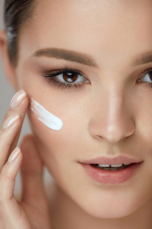 뷰티 화장품. 매력적인 섹시 한 웃는 소녀 얼굴의 근접 촬영 화장품 제품, 스킨 케어 크림의 스트라이프. 부드러운 피부와 자연스러운 메이크업 아름