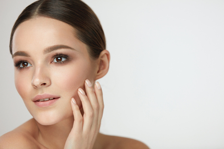 Woman Beauty Face Care. Closeup Of Attractive Young Female Touching Fresh Smooth Soft Facial Skin. Portrait Of Beautiful Sexy Girl Model With Natural Makeup Touching Face With Hand. High Resolution