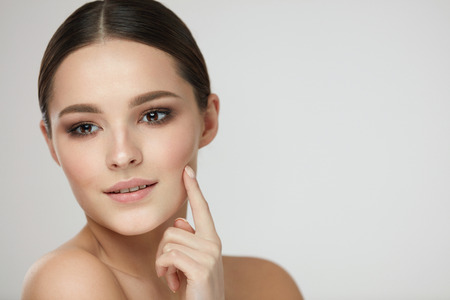 Woman Skin Beauty. Closeup Of Beautiful Healthy Woman Caressing Face With Finger. Portrait Of Attractive Young Female Model Touching Facial Skin On Grey Background. Cosmetic Concept. High Resolution